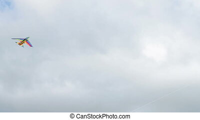 Two kites flying in cloudy sky