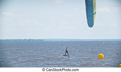 Two kitesurfers flying past each other on kiteboards over...