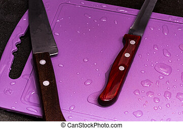 Two knives lie on a cutting board in a dark sink in the kitchen. The board is covered with drops of water.