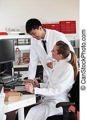 Two lab technicians discussing their work