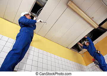 Two laborers working on ceiling piping