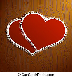 Two lacy red hearts on a wooden background