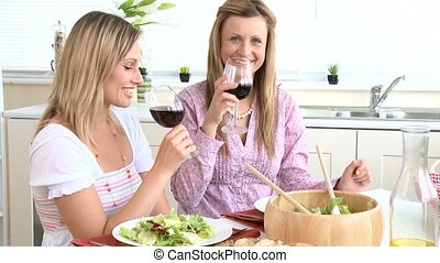 two ladies eating salad with wine
