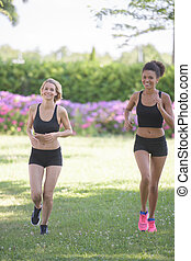 two ladies jogging in park