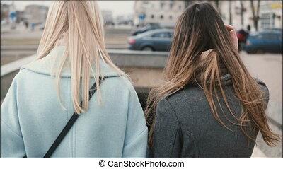 Two ladies walk down to a pedestrian tunnel. Gilfriends in...