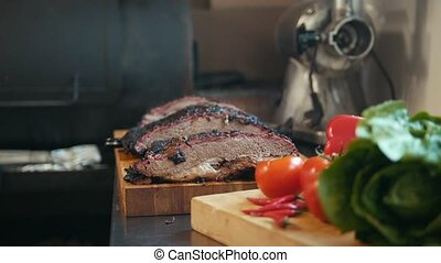 Two large pieces of smoked brisket meat on a wooden board