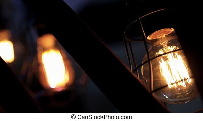 Two large vintage electric lights burn in the dark outside....