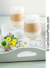 Two latte coffee with spring flowers