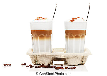two latte macchiato with chocolate powder in a cupholder with coffee beans and spoons on white background