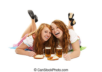 two laughing bavarian girls with beer and pretzels on the floor on white background