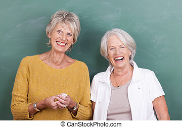 Two laughing elderly women standing side by side facing the...