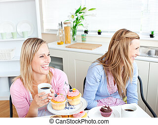 Two laughing female friends eating pastries and drinking coffee in the kitchen at home
