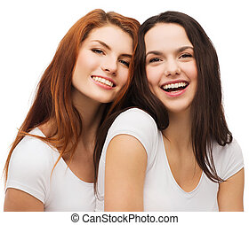 two laughing girls in white t-shirts hugging