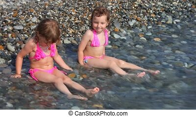 two laughing little girls sitting on pebble beach with sea surf