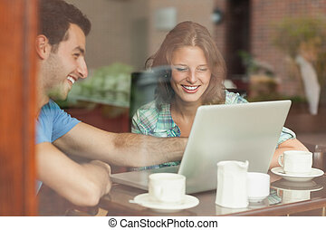 Two laughing students looking at laptop