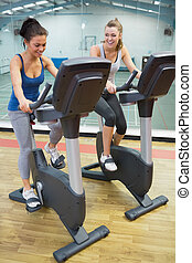 Two laughing women on exercise bikes