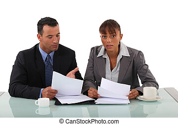 Two lawyers going over notes