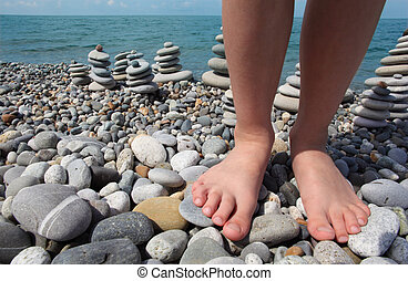 two legs and stone stacks on pebble beach - two childish...