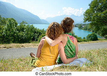 two lesbians in nature admire the lake of Annecy