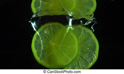 Two lime slices fall under water super slow motion shot. Black background