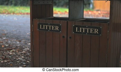 Smooth backward 4k video of two wooden litter bins in the middle of a park surrounded by fallen autumn leaves, and with a road behind them