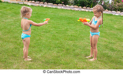 Two little adorable girls playing with water guns in the ...