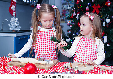 Two little adorable girls preparing gingerbread cookies for Christmas
