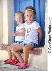 Two little adorable girls sitting on doorstep of old house...