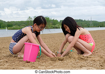 Two little Asian girls playing sand at beach