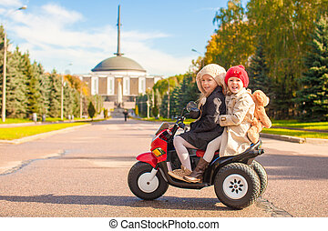 Two Little beautiful sisters sitting on toy motorcycle in autumn park