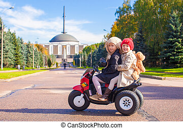 Two Little beautiful sisters sitting on toy motorcycle in big park
