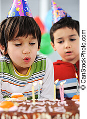 Two little boys blowing candles on cake, happy birthday party