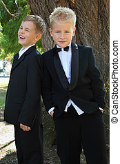 two little boys dressed in tuxedo standing near tree at...