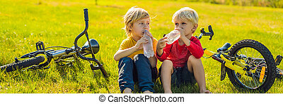 Two little boys drink water in the park after riding a bike BANNER, LONG FORMAT
