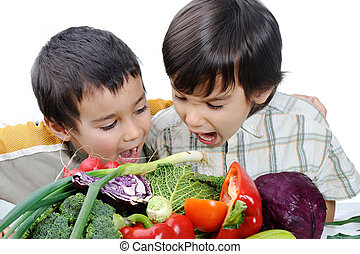 Two little boys eating vegetables
