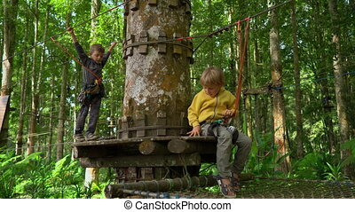 Two little boys in a safety harness climb on a route in a...