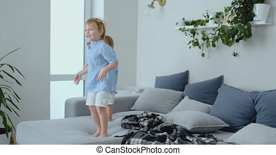 Two little boys jumping on the couch and having fun. Joy,...