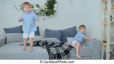 Two little boys jumping on the couch and having fun.