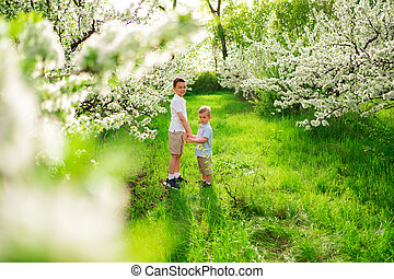 two little boys on the lawn among the flowering trees. life in the countryside.