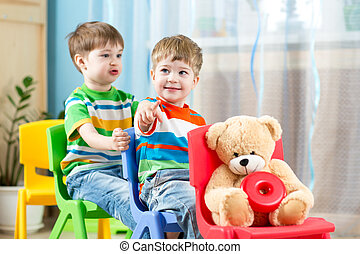 Two little boys playing role game in daycare - Two cute...