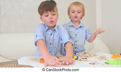 Two little boys playing with dough and learning how to bake