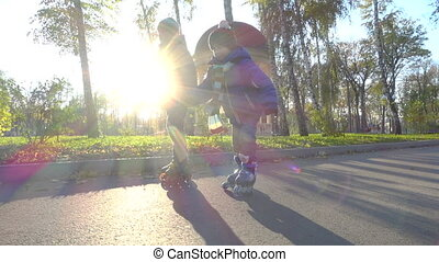 Two little boys ride in autumn park on rollers, slow motion