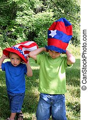 Two little boys wearing 4th of July hats