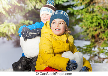 Two little boys with big snowballs in the forest