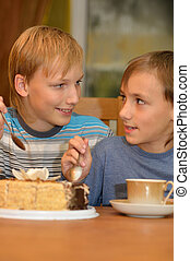 Two little brothers eat cake