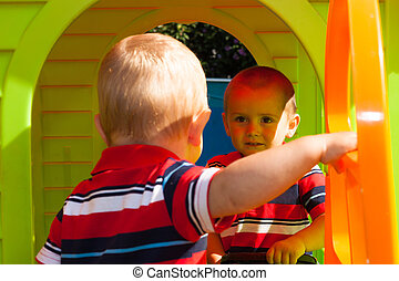 Two little brothers in playhouse