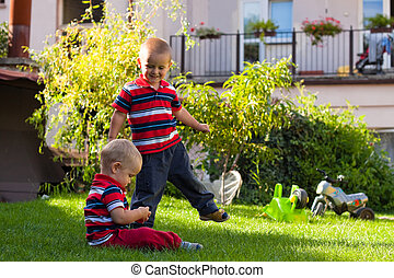 Two little brothers play outdoors
