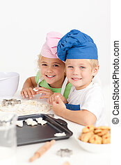 Two little chefs preparing cookies in the kitchen