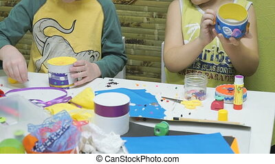 Two little child make crafts toy from cardboard