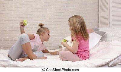 two little children girls eat green fresh apples sitting on...
